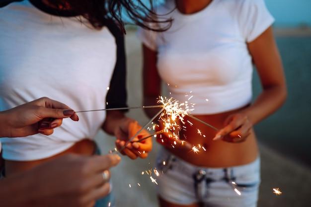 Le stelle filanti nelle mani di giovani ragazze sulla spiaggia. tre ragazze che godono del partito sulla spiaggia con le stelle filante. vacanze estive, vacanze, relax e lifestyle concept.