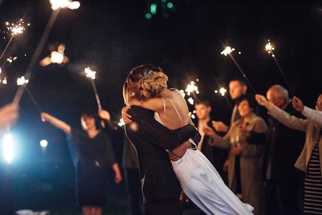 Sparklers al matrimonio degli sposi nelle mani di ospiti gioiosi