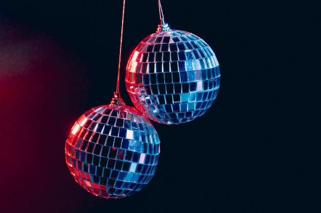 Sfere scintillanti della discoteca che pendono nell'aria contro il nero