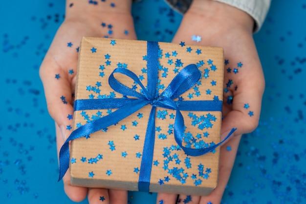 Confezione regalo scintillante avvolta in carta artigianale e legata con fiocco nelle mani del bambino