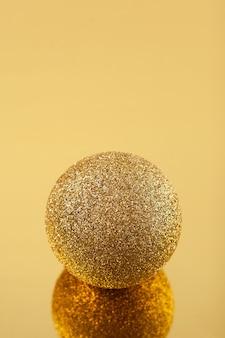 Sfera dorata scintillante su sfondo specchio dorato. elementi di design.