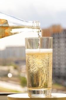 L'acqua frizzante viene versata in un bicchiere, le bollicine frizzanti in un bicchiere