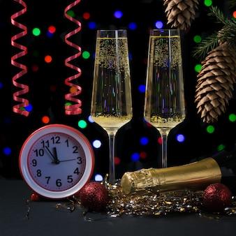 Bicchieri di spumante stelle filanti rosse e orologio rosso. felice anno nuovo