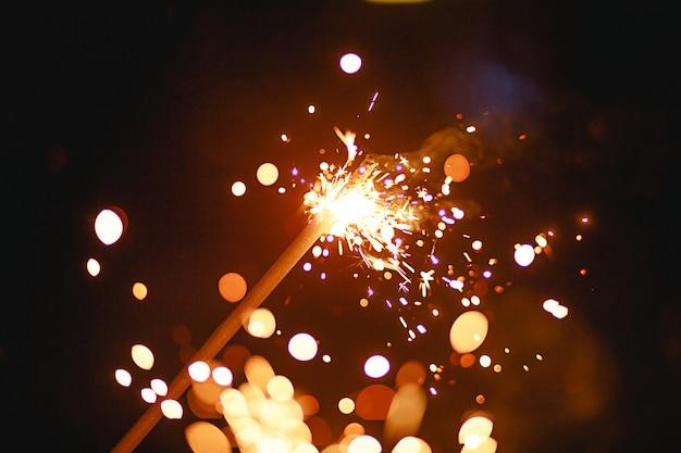 Scintille e luce dalle stelle filanti nel buio con bokeh e fumo giallo e arancione brillante. festosa trama di fuoco, sfondo per capodanno e natale.