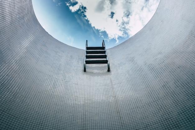 Scala sparsa di una piscina vuota, vista dal basso, sfondo minimalista delle mattonelle.