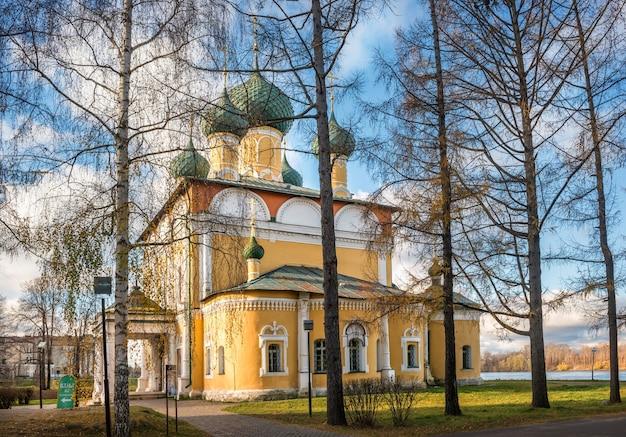 Cattedrale spaso-preobrazhensky del cremlino a uglich attraverso i tronchi degli alberi sotto i raggi del sole autunnale
