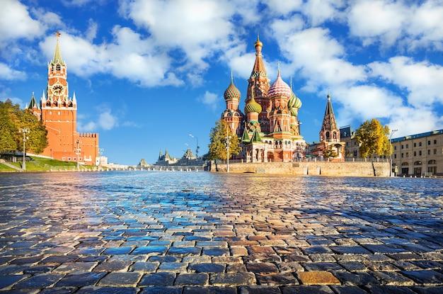 Torre spasskaya e cattedrale di san basilio sulla piazza rossa di mosca e pavimentazione bagnata all'inizio dell'autunno mattina