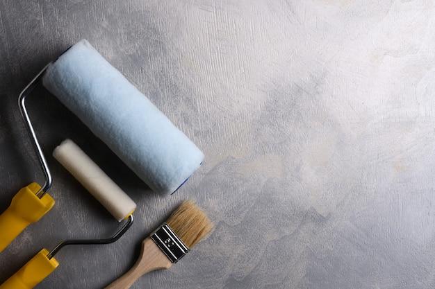 Spatole per stucco e pennelli e rulli per pittura su fondo grigio cemento. vista dall'alto