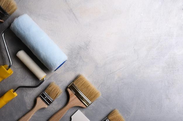 Spatole per l'applicazione di stucco e pennelli e rulli per la pittura su un tavolo di cemento grigio. vista dall'alto