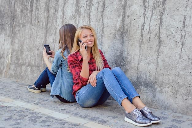 Parla, racconta, ascolta, gossip, riposa, rilassa, stile bella felice bella bella bella dolce carina deliziosa signora che parla al telefono un'altra ragazza affascinante che legge notizie su internet
