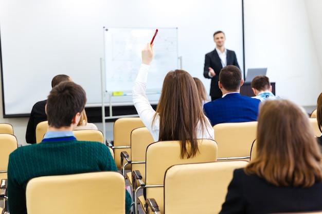 Relatore che parla con il pubblico e risponde alle domande sulla riunione di lavoro nella sala conferenze