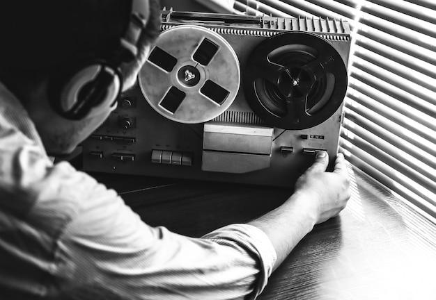 L'agente speciale ascolta sul registratore a bobine. agente intercettazioni in cuffia. spionaggio del kgb delle conversazioni. periodo della guerra fredda. foto in bianco e nero.