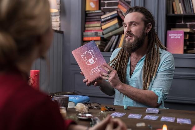 Libro speciale. felice simpatico uomo che sorride mentre parla dell'energia della salute