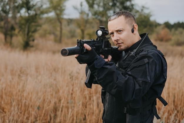 Soldato della forza speciale in uniforme nera che mira un fucile d'assalto