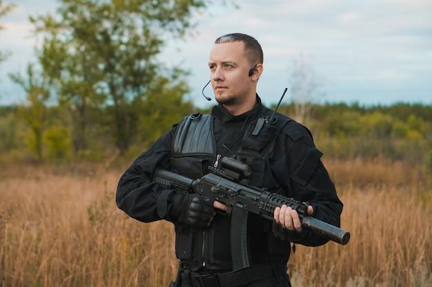 Soldato delle forze speciali in uniforme nera con un fucile d'assalto