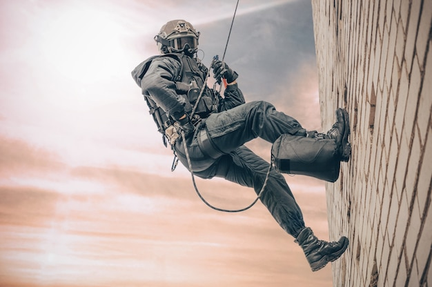 Il combattente delle forze speciali scende da un grattacielo per prendere d'assalto l'appartamento. swat, polizia, concetto di antiterrorismo.