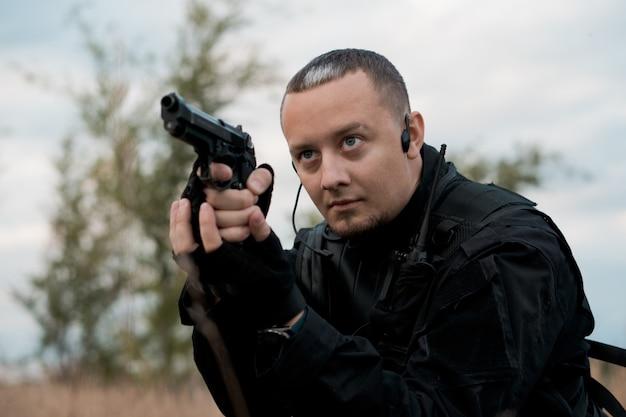 Soldato delle forze speciali in uniforme nera che mira una pistola
