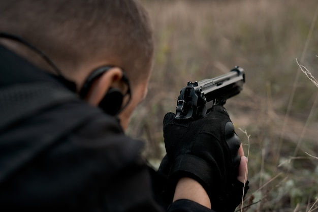 Soldato delle forze speciali in uniforme nera sdraiato e puntando una pistola