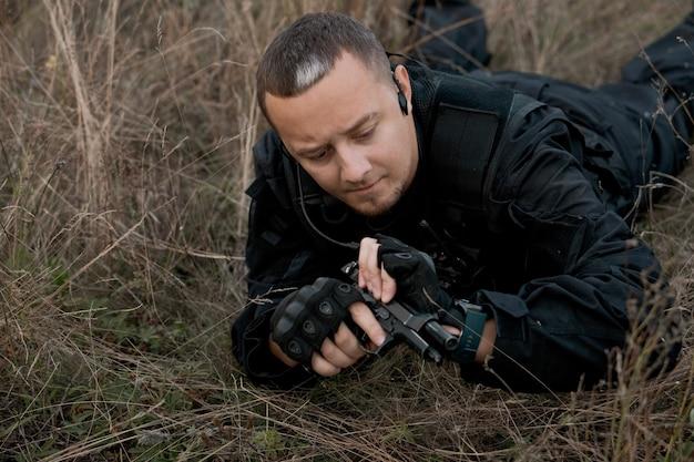 Soldato delle forze speciali in uniforme nera sdraiato e ricarica una pistola