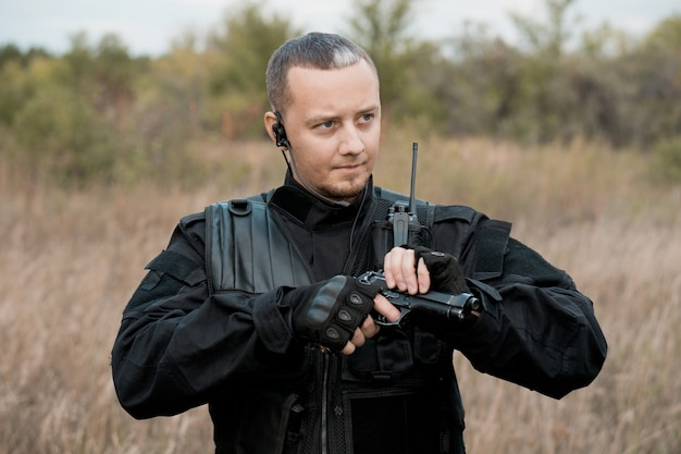 Soldato delle forze speciali in uniforme nera che ricarica una pistola