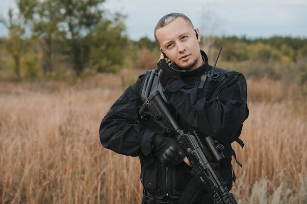 Soldato delle forze speciali in uniforme nera con un fucile d'assalto che parla alla radio