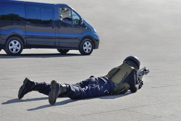 Soldato delle forze speciali sdraiato a terra che mira da un fucile d'assalto vicino all'auto
