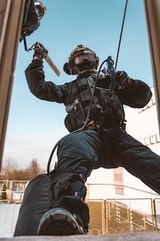 Soldato delle forze speciali fa irruzione nell'edificio attraverso la finestra. sessioni di allenamento della squadra swat