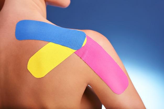 Nastro fisioterapico speciale messo sul braccio ferito su sfondo bianco