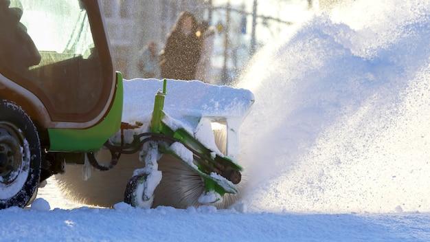 La macchina speciale della neve rimuove la neve sulla strada della città. trasporto invernale