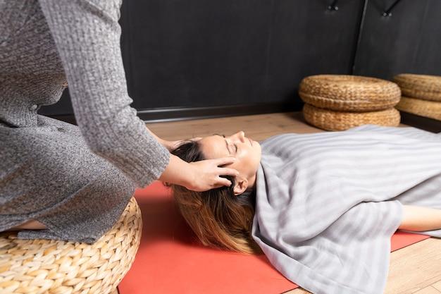 Terapia speciale. processo di massaggio rilassante alla testa. donna che fa il massaggio con le mani.
