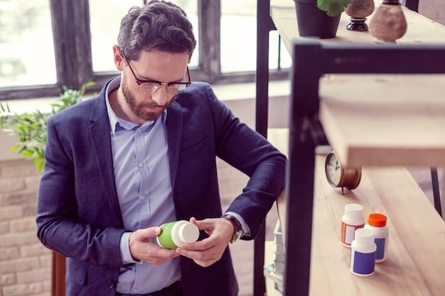 Vitamine speciali. simpatico uomo serio che legge un'iscrizione sulla bottiglia mentre vuole sapere di cosa si tratta