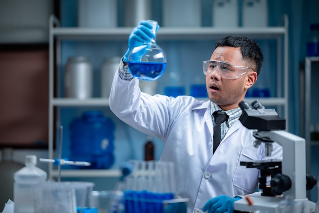 Lo speciale giovane scienziato o ricercatore che guarda la soluzione chimica attraverso la provetta per l'esperimento del vaccino in via di sviluppo presso il moderno laboratorio biologico