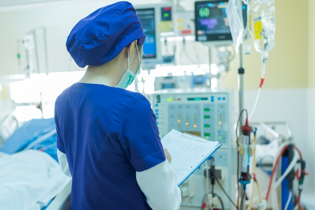 Lo specialista sta controllando l'attrezzatura per la terapia sostitutiva renale continua, la pompa di iniezione e la macchina per emodialisi.