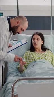 Medico specialista monitoraggio donna malata che esamina il pulsossimetro scrivendo il trattamento della malattia negli appunti. paziente che riposa a letto mentre l'infermiera nera fa comodo il letto nel reparto ospedaliero