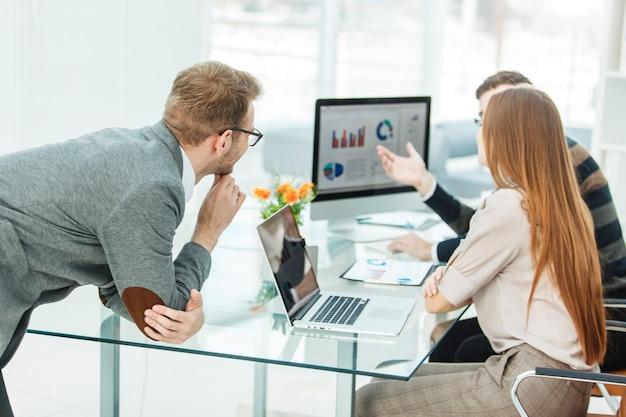 Specialista in finanza e team professionale di affari che fa analisi di rapporti di marketing, in un ufficio moderno