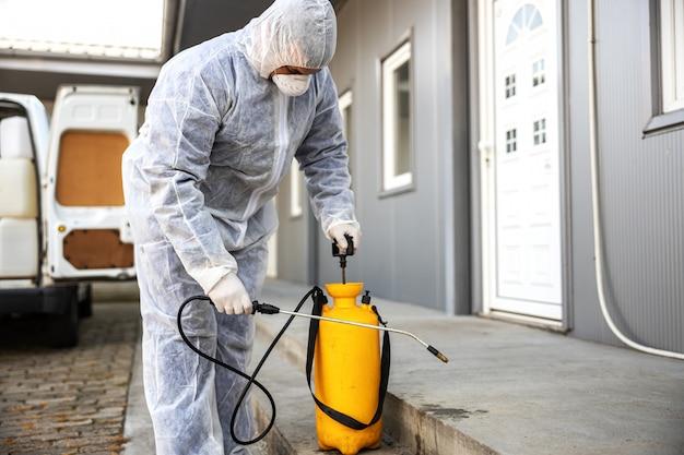 Specialista in tute ignifughe che prepara per la pulizia e la disinfezione di cellule epidemiche di coronavirus