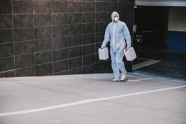Specialista in tute ignifughe preparazione per la pulizia e la disinfezione di cellule covid-19 epidemia, rischio per la salute di pandemia mondiale.