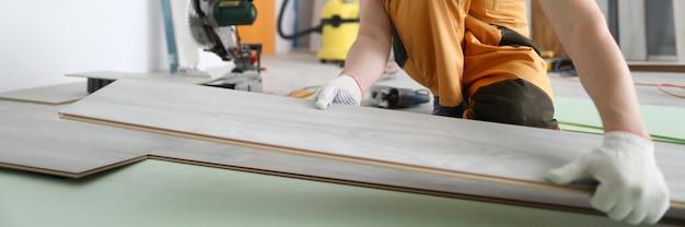 Lo specialista tiene il laminato in mano e lo appoggia sul pavimento. l'uomo in tuta e casco fa le riparazioni in camera.