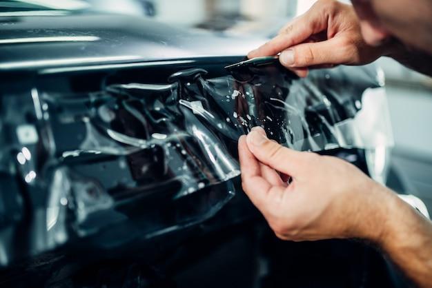 Lo specialista installa la pellicola protettiva per la vernice dell'auto