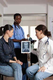 Medico specialista radiologo che analizza radiografia clinica con paziente donna