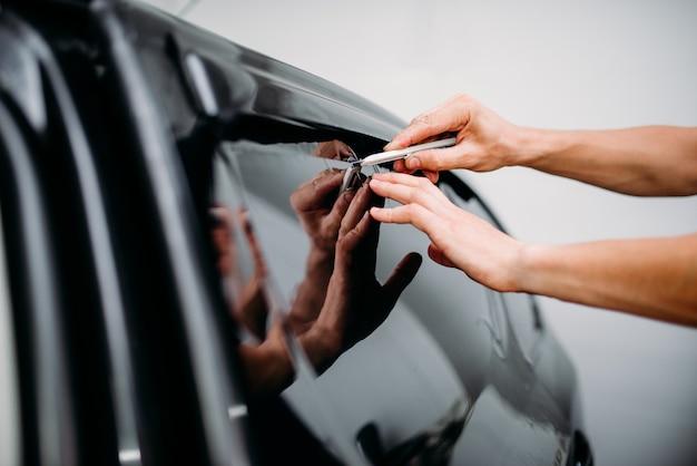 Lavoro specialistico con auto, installazione di pellicole coloranti