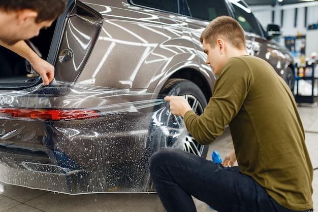 Gli specialisti applicano la pellicola di protezione dell'auto sul paraurti posteriore. installazione di rivestimento che protegge la vernice dell'automobile dai graffi. veicolo nuovo in garage, messa a punto