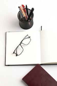 Occhiali o occhiali da vista e diario su sfondo bianco