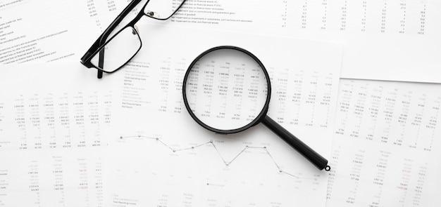 Occhiali e lente d'ingrandimento sui dati finanziari. concetto di ricerca aziendale e finanziaria.