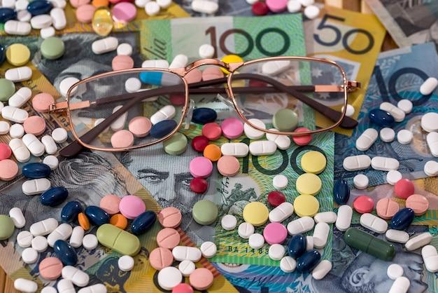 Occhiali con pillole colorate sui dollari australiani