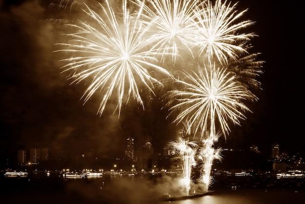Spettacolari fuochi d'artificio che schizzano nel cielo notturno sopra la baia in color seppia Foto Premium