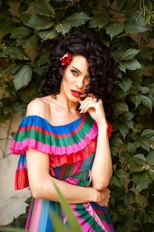 Bella donna europea sensuale spettacolare con capelli scuri arricciati in un vestito estivo in città