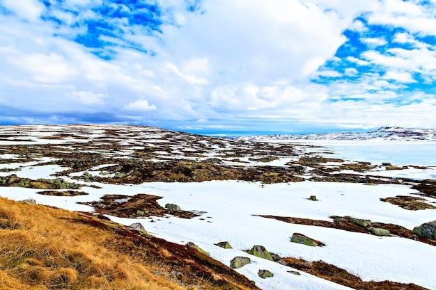 Spettacolare vista delle nuvole sul lago ghiacciato e sulle montagne