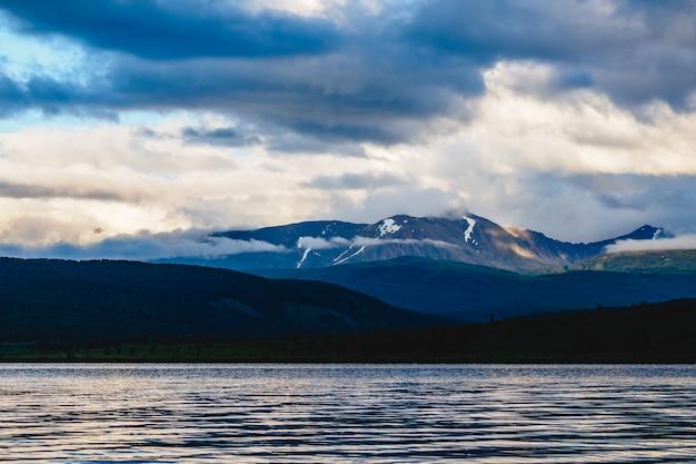 Spettacolare vista di una catena montuosa in nuvole vicino a un lago nel distretto di ulagansky della repubblica di altai, russia