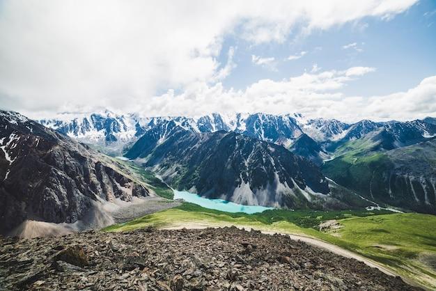 Vista spettacolare sulla valle panoramica con un grande e bellissimo lago di montagna circondato da gigantesche catene innevate e ghiacciai